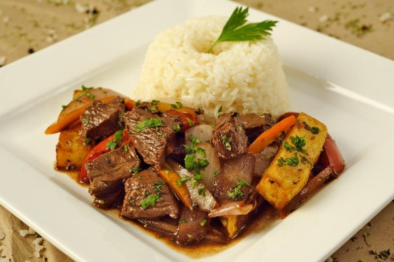 lomo saltado served with white rice and cilantro