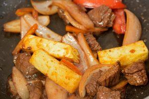 tomatos, pepper, potato beef strips, onion fry in a wok