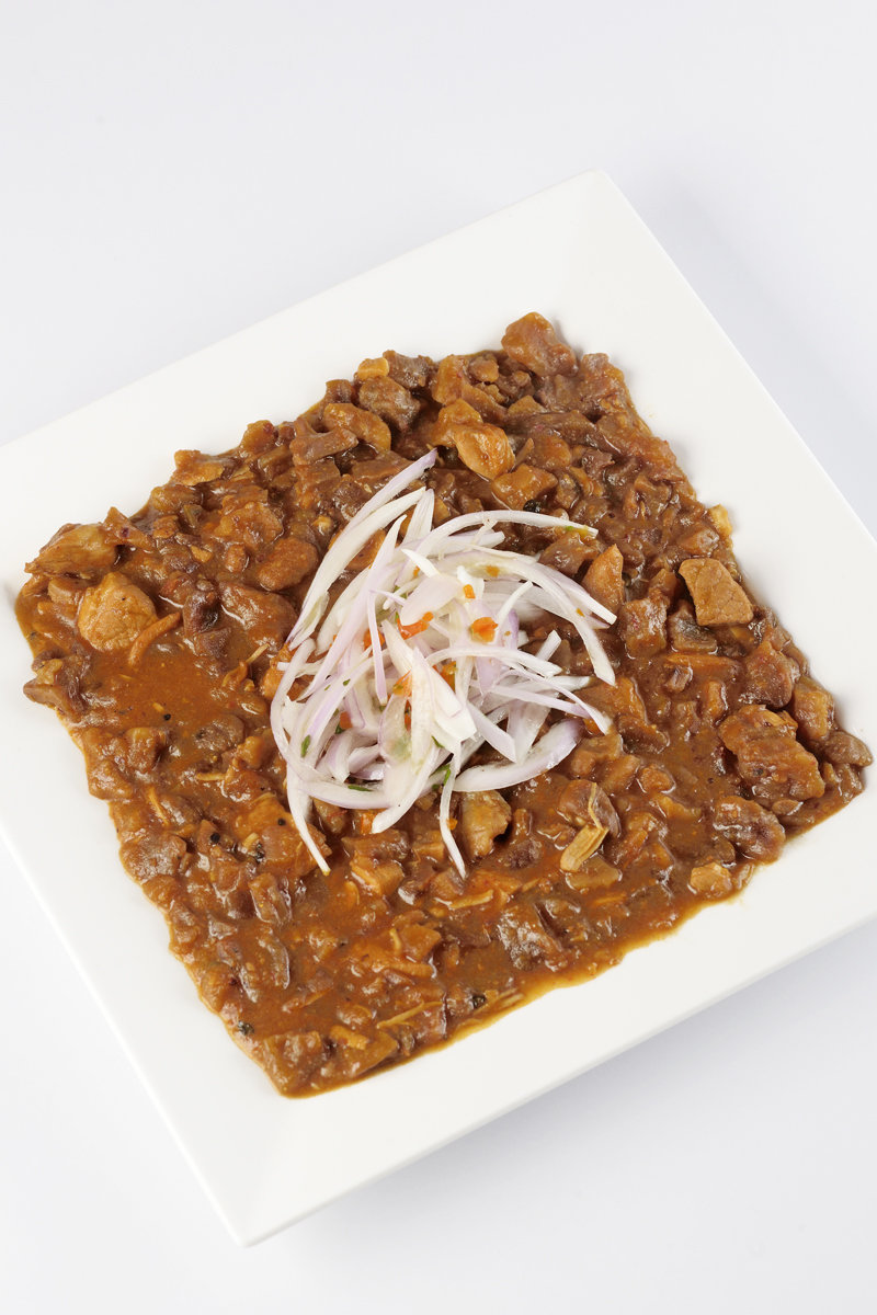 Carapulcra Peruvian stew on plate with onion salad