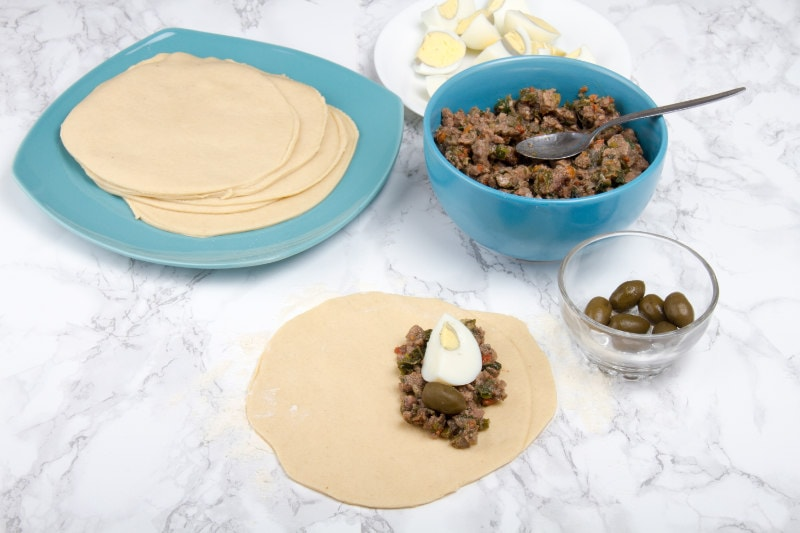 adding meat stew and egg to empanada dough circle 1