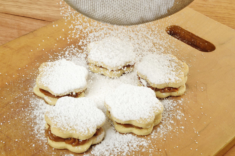 sprinkle the powdered sugar over the alfajores