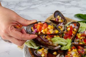 hand holding steamed mussel and corn