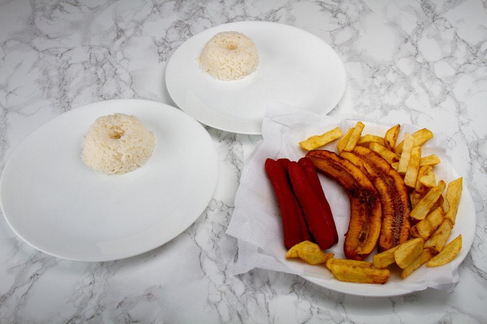 Arrange The Potatoes Rice And Salchicha On Plates